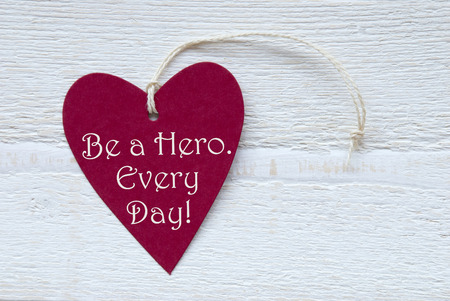english text: One Red Heart Label Or Tag With White Ribbon On White Wooden Background With English Text Be A Hero Every Day Vintage Retro Or Rustic Style Stock Photo