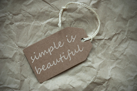 simple life: One Beige Label Or Tag With White Ribbon On Crumpled Paper Background With English Life Quote Simple Is Beautiful Vintage Or Retro Style With Frame