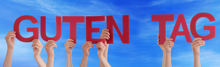 guten tag: Many Caucasian People And Hands Holding Red Straight Letters Or Characters Building The German Word Guten Tag Which Means Good Day On Blue Sky Stock Photo