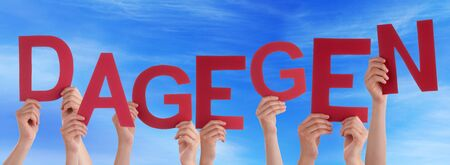 dislike it: Many Caucasian People And Hands Holding Red Letters Or Characters Building The German Word Dagegen Which Means Against It On Blue Sky