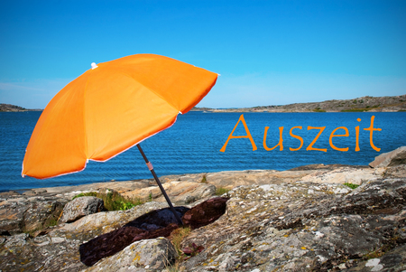 german ocean: Swedish Coastline Bohuslan Archipelago Close To Gothenburg Swedish West Coast With Rocks And Cliffs And Beach With Orange Parasol And German Text Auszeit Means Downtime With Ocean And Open Sea Sunny Weather With Blue Sky Stock Photo