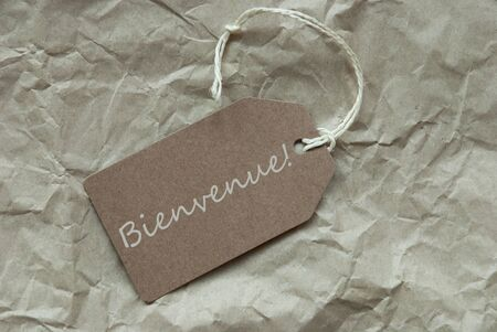 french text: One Beige Label Or Tag With White Ribbon On Crumpled Paper Background With French Text Bienvenue Means Welcome Vintage Or Retro Style Stock Photo