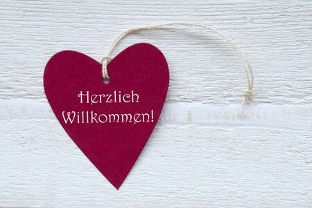 willkommen: One Red Heart Label Or Tag With White Ribbon On White Wooden Background With German Text Herzlich Willkommen Means Happy Welcome Vintage Retro Or Rustic Style