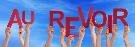 despedida: Muchas personas de raza blanca y las manos de la explotaci�n agr�cola roja directa letras o caracteres construcci�n de la Palabra francesa Au Revoir Qu� significa adi�s en el cielo azul