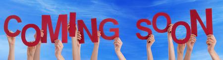 Viele Menschen Caucasian And Hands Holding Red Buchstaben oder Zeichen Gebäude das englische Wort Demnächst auf blauem Himmel