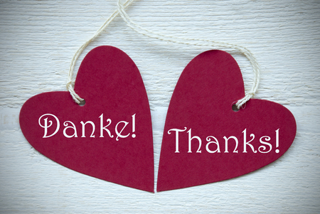 thankfulness: Two Red Hearts Label Or Tag With White Ribbon On White Wooden Background With German Text Danke Means Thank You And English Text Thanks Vintage Retro Or Rustic Style With Frame Stock Photo