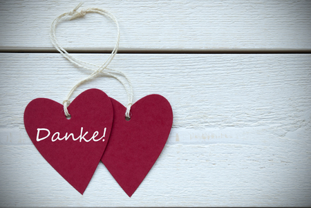 thankfulness: Two Red Hearts Label With White Ribbon On White Wooden Background With German Text Danke Means Thank You Vintage Retro Or Rustic Style With Frame Stock Photo