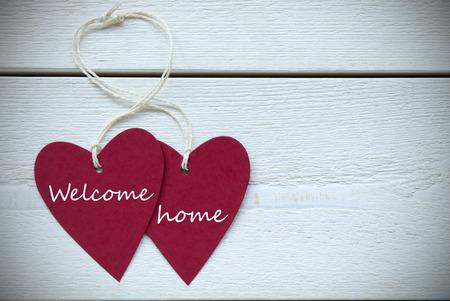 Twee Rode Harten etiket met wit lint op een witte houten achtergrond met Engels Tekst Welcome Home Vintage Retro Of Rustieke stijl Met Frame
