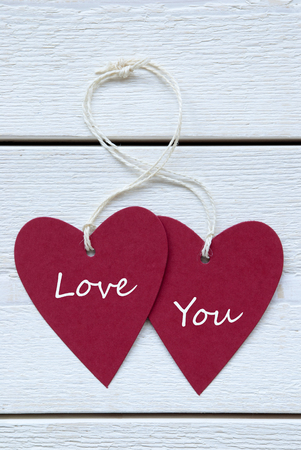 Vertical Image With Two Red Hearts Label With White Ribbon On White Wooden Background With English Text Love You Vintage Retro Or Rustic Style photo