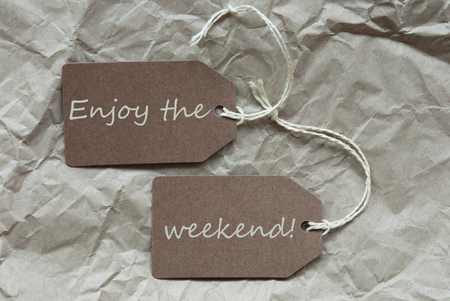 creasy: Two Brown Labels Or Tags With White Ribbon On Crumpled Paper Background With English Life Quote Enjoy The Weekend Vintage Or Retro Style