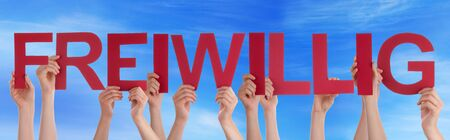 voluntary: Many Caucasian People And Hands Holding Red Straight Letters Or Characters Building The German Word Freiwillig Which Means Voluntary On Blue Sky Stock Photo