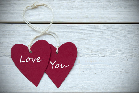 Two Red Hearts Label With White Ribbon On White Wooden Background With English Text Love You Vintage Retro Or Rustic Style With Frame photo