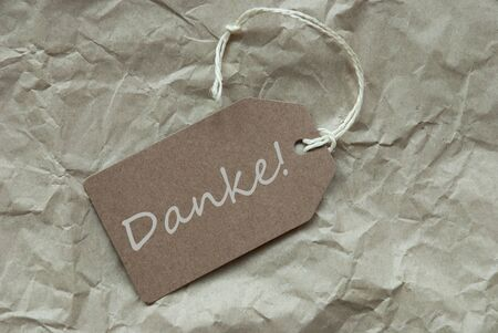 thankfulness: One Beige Label Or Tag With White Ribbon On Crumpled Paper Background With German Text Danke Means Thank You Vintage Or Retro Style Stock Photo
