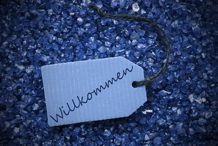 willkommen: One Blue Label Or Tag With Black Ribbon On Blue And Purple Small Stones As Background With German Text Willkommen Means Welcome With Frame