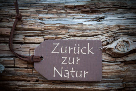 natur: One Brown Label Or Tag With Black Ribbon On Brown Wooden Background With German Text Zurueck Zur Natur Which Means Back To Nature Vintage Shabby Chic Retro Or Rustic Style With Frame