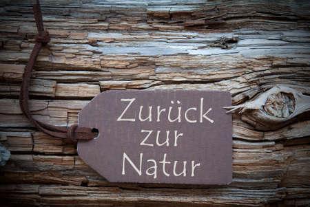 natur: Una Label Brown o tag con nastro nero su sfondo di legno marrone con testo tedesco Zurueck Zur Natur che significa Back To Nature Vintage Shabby Chic Retro Oppure stile rustico con la struttura Archivio Fotografico