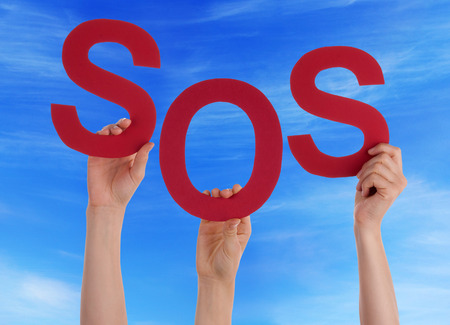 Many Caucasian People And Hands Holding Red Letters Or Characters Building The English Word Sos On Blue Sky Stock Photo
