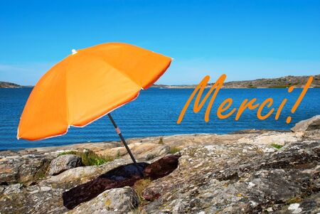 french text: Swedish Coastline Bohuslan Archipelago Close To Gothenburg Swedish West Coast With Rocks And Cliffs And Beach With Orange Parasol And French Text Merci Means Thank You With Ocean And Open Sea Sunny Weather With Blue Sky Stock Photo