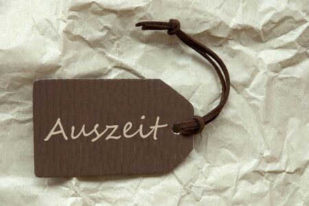 auszeit: One Brown Label Or Tag With Brown Ribbon On Crumpled Paper Background With German Text Auszeit Means Downtime Vintage Or Retro Style