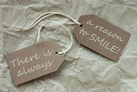 creasy: Two Beige Labels Or Tags With White Ribbon On Crumpled Paper Background With English Life Quote There Is Always A Reason To Smile Vintage Or Retro Style