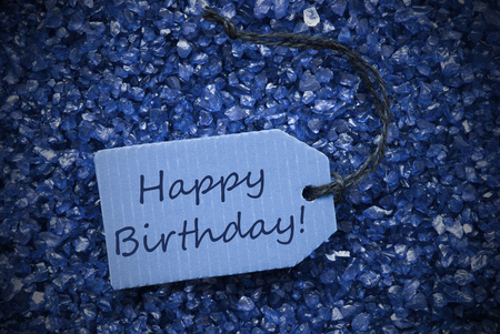 small stones: One Blue Label Or Tag With Black Ribbon On Blue And Purple Small Stones As Background With English Text Happy Birthday With Frame Stock Photo