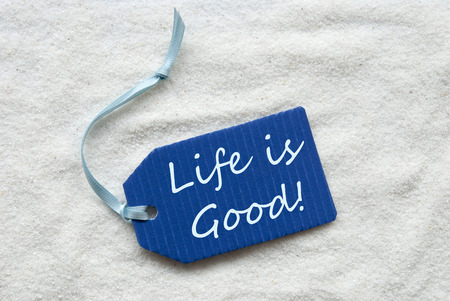 One Blue Label Or Tag With Light Blue Ribbon On White Sand Background With English Quote Life Is Good