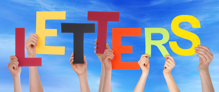 alphabetic character: Many Caucasian People And Hands Holding Colorful Letters Or Characters Building The English Word Letters On Blue Sky Stock Photo