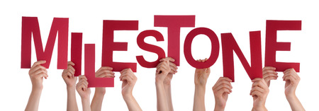 Many Caucasian People And Hands Holding Red Letters Or Characters Building The Isolated English Word Milestone On White Background