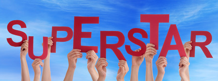 superstar: Many Caucasian People And Hands Holding Red Letters Or Characters Building The English Word Superstar On Blue Sky