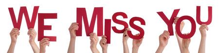 Veel blanke mensen en handen die rode letters of tekens Gebouw De Geïsoleerde Engels woord We missen je op een witte achtergrond