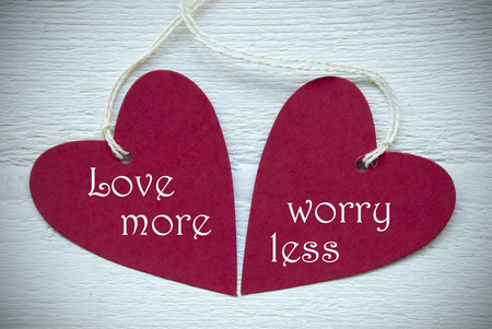Two Red Hearts Label Or Tag With White Ribbon On White Wooden Background With English Text Love More Worry Less Vintage Retro Or Rustic Style With Frame
