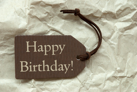 creasy: One Brown Label Or Tag With Brown Ribbon On Crumpled Paper Background With English Text Happy Birthday Vintage Or Retro Style