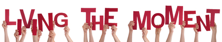 living moment: Many Caucasian People And Hands Holding Red Letters Or Characters Building The Isolated English Word Living The Moment On White Background
