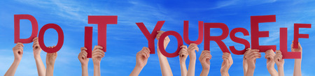 Many Caucasian People And Hands Holding Red Letters Or Characters Building The English Word Do It Yourself On Blue Sky photo