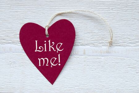 like english: One Red Heart Label Or Tag With White Ribbon On White Wooden Background With English Text Like Me Vintage Retro Or Rustic Style