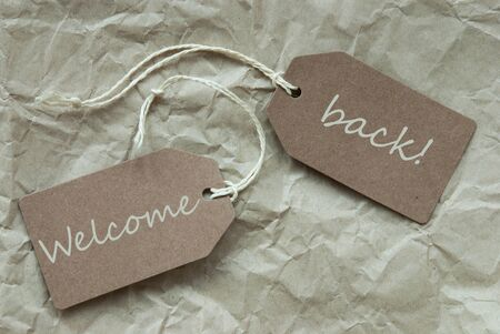 warm welcome: Two Beige Labels Or Tags With White Ribbon On Crumpled Paper Background With English Text Welcome Back Vintage Or Retro Style