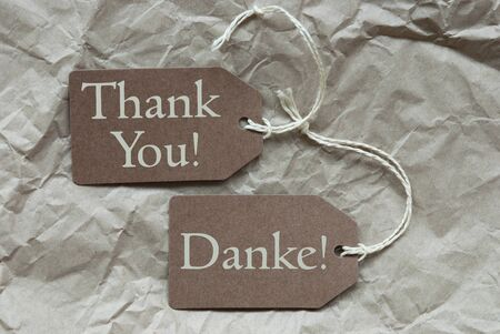 Two Brown Labels Or Tags With White Ribbon On Crumpled Paper Background With German Text Danke Means Thank You And English Thank You Vintage Or Retro Style photo