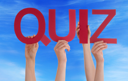 Many Caucasian People And Hands Holding Red Straight Letters Or Characters Building The English Word Quiz On Blue Sky photo