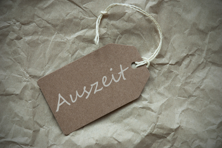 auszeit: One Beige Label Or Tag With White Ribbon On Crumpled Paper Background With German Text Auszeit Means Downtime Vintage Or Retro Style With Frame