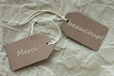 french text: Two Beige Labels Or Tags With White Ribbon On Crumpled Paper Background With French Text Merci Beaucoup Means Thank You Vintage Or Retro Style