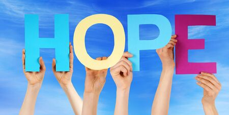 hope: Many Caucasian People And Hands Holding Colorful Straight Letters Or Characters Building The English Word Hope On Blue Sky