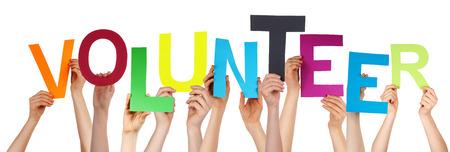 Viele Menschen kaukasischen Und Hände halten bunte Buchstaben oder Zeichen Building Der Isolated English Word Volunteer auf weißem Hintergrund