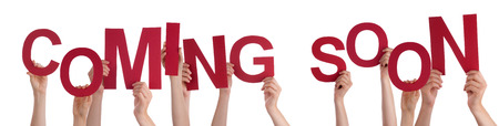 Many Caucasian People And Hands Holding Red Letters Or Characters Building The Isolated English Word Coming Soon On White Background photo