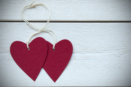 Two Empty Red Hearts Label With White Ribbon On White Wooden Background. Copy Space Your Text Here Or Free Text For Advertisement Vintage Retro Or Rustic Style With Frame photo