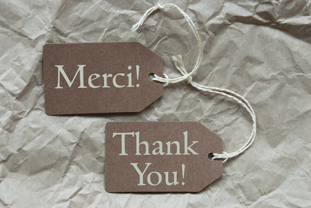french text: Two Brown Labels Or Tags With White Ribbon On Crumpled Paper Background. French Text Merci Means Thank You And English Thank You Vintage Or Retro Style