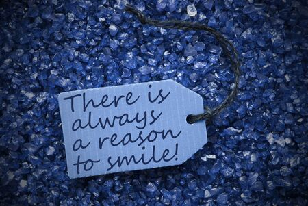 small stones: One Blue Label Or Tag With Black Ribbon On Blue And Purple Small Stones. Background With English Life Quote There Is Always A Reason To Smile With Frame Stock Photo