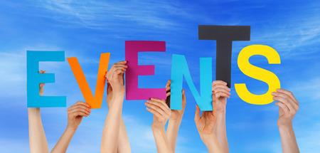 Veel blanke mensen En Handen die kleurrijke letters of tekens bouwen van het Engels woord Events Op Blauwe Hemel