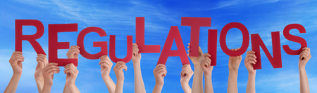 guideline: Many Caucasian People And Hands Holding Red Letters Or Characters Building The English Word Regulations On Blue Sky