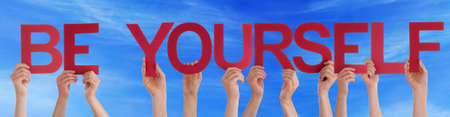 be yourself: Many Caucasian People And Hands Holding Red Straight Letters Or Characters Building The English Word Be Yourself On Blue Sky