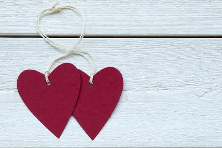 Two Empty Red Hearts Label With White Ribbon On White Wooden Background photo